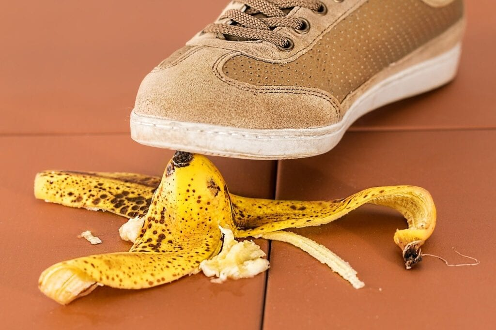 A brown shoe about to step on a banana peel