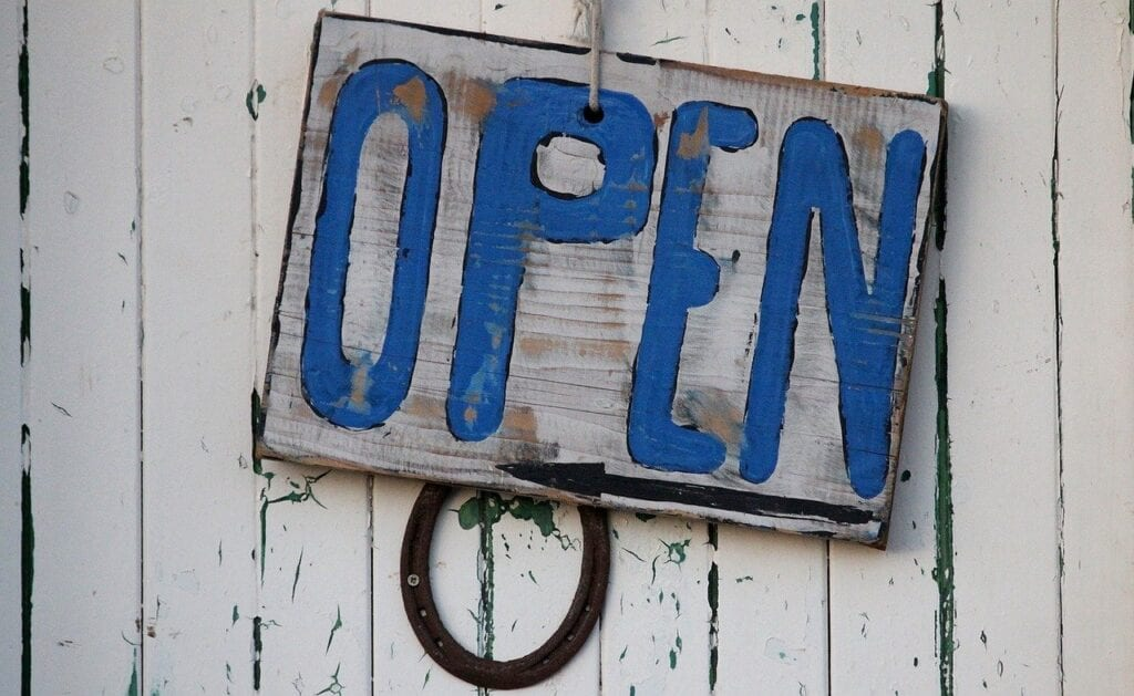 A blue, rustic open sign