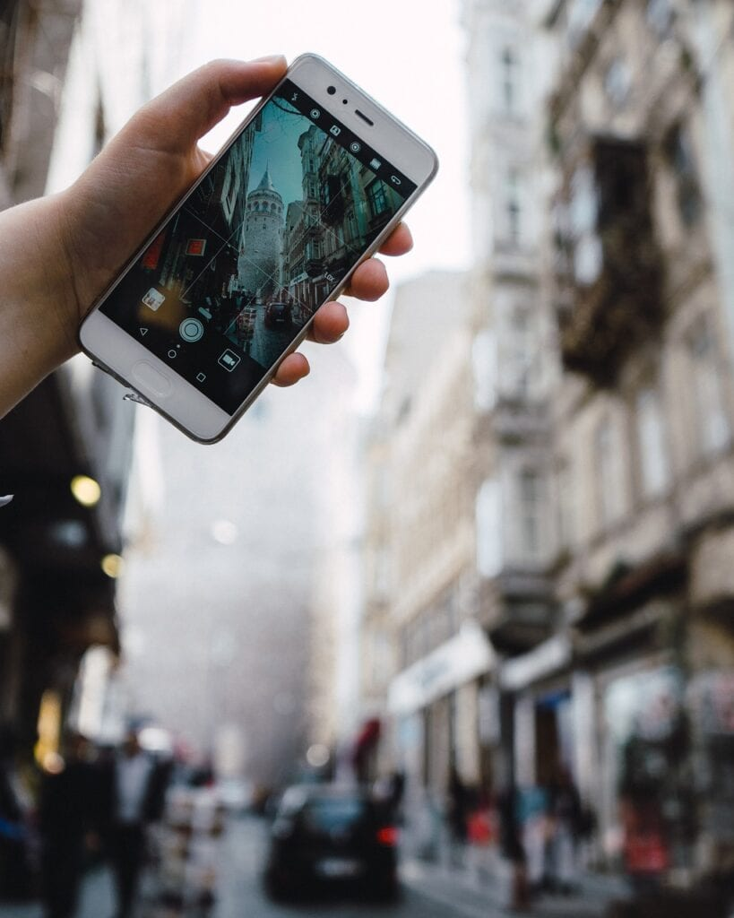 A traveler holds up a phone to take a picture on a crowded Turkish street