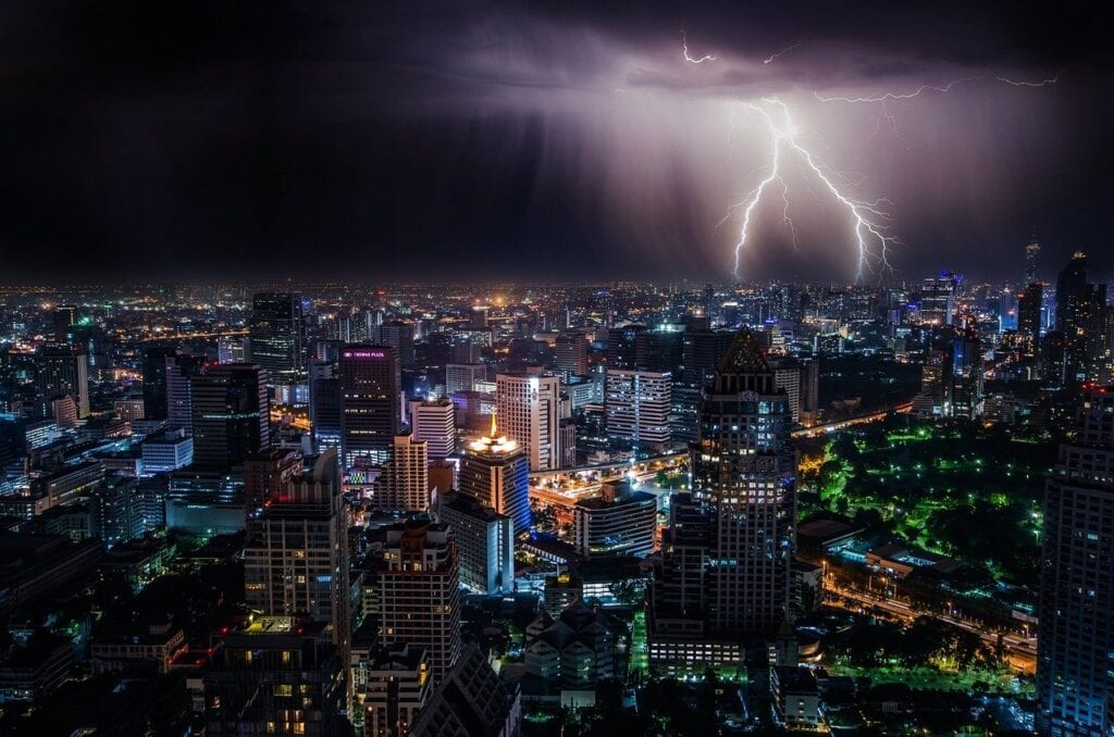 Lightning strikes in the distance of a city at night