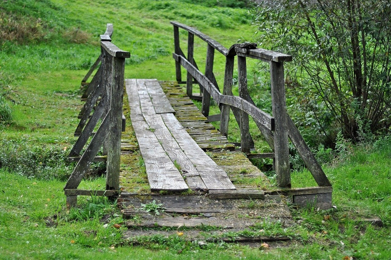 A wooden pathbridge fords a creek green field
