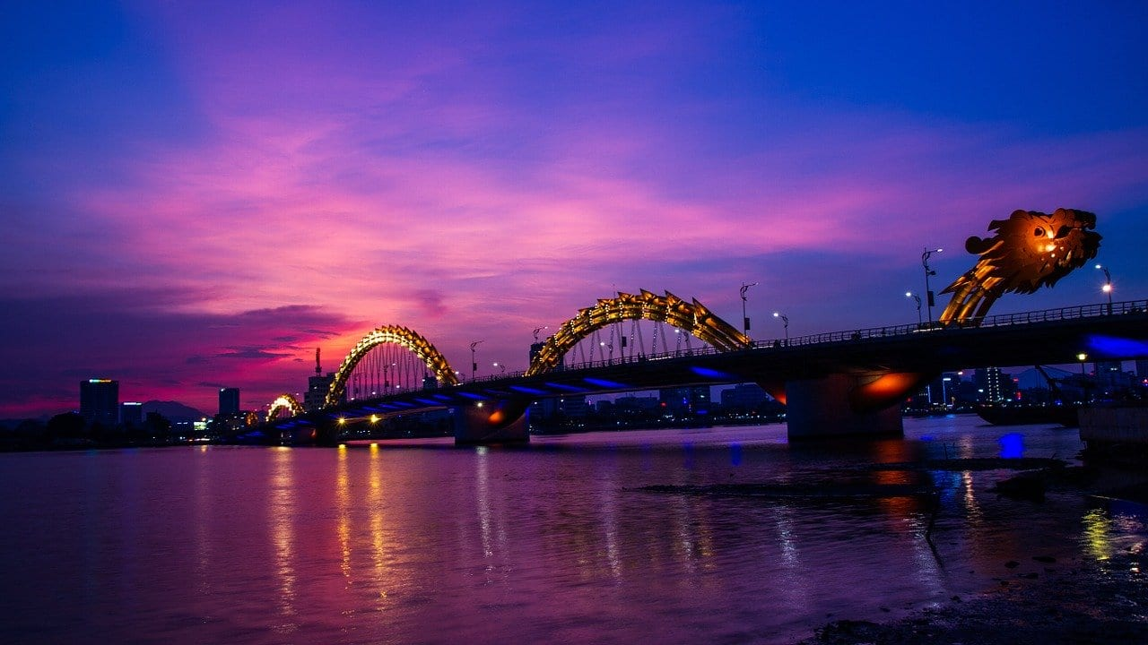 Dragon bridge in Vietnam. The sky turns pink and purple in the distance, the dragon bridge in the foreground