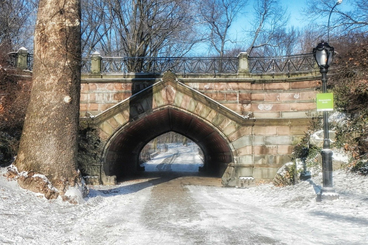 A stone Path Bridge in Central Park covered in snow