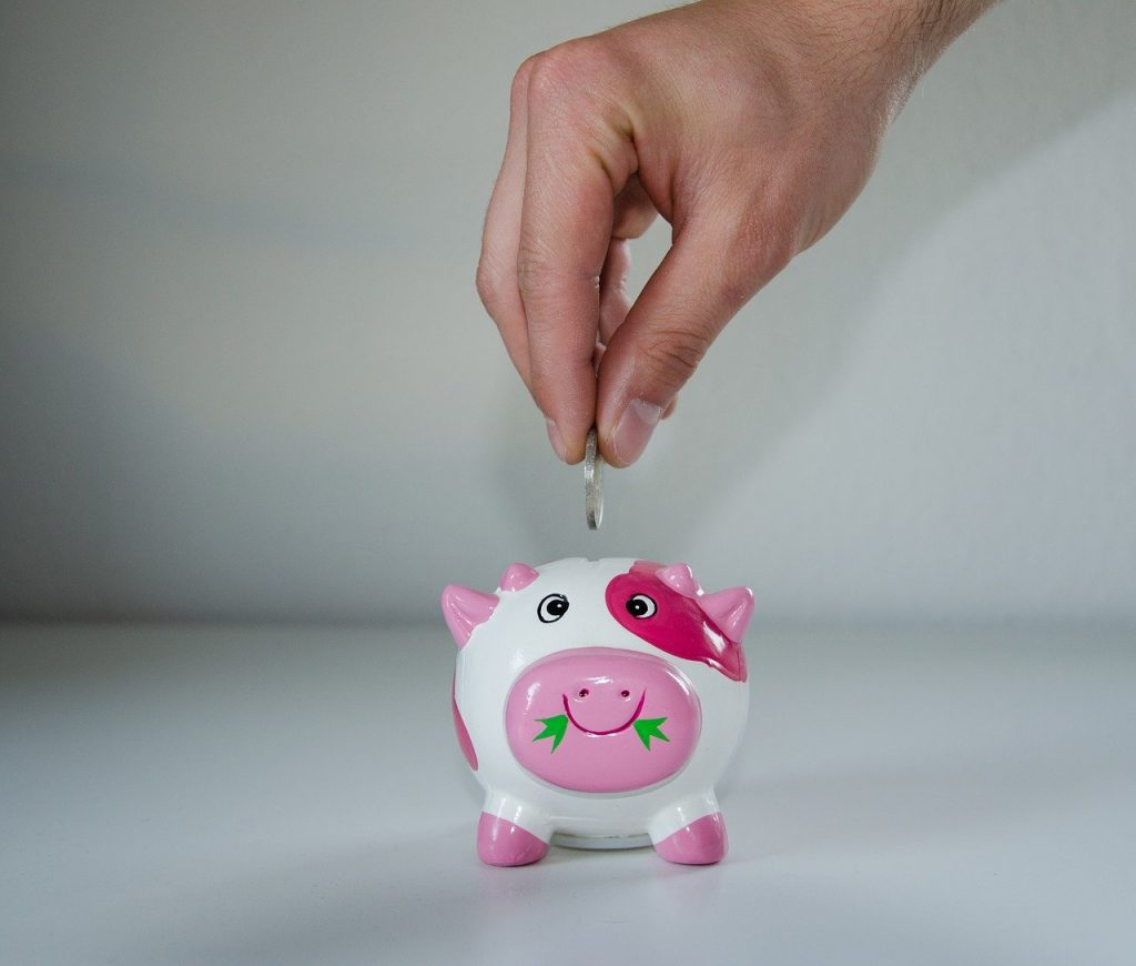 Money being placed in a pink piggy bank