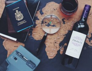 Retirement traveler searches for a place to travel. Blue world map covered with a passport, camera, magnifying glass, and a bottle of wine.